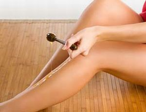 woman putting depilatory wax on her leg like honey